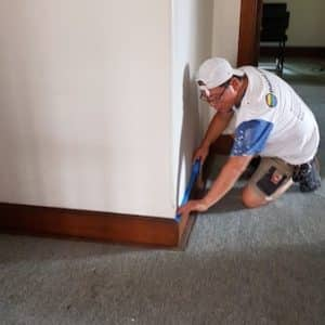 Lining skirting board with painting tape to ensure straight lines.